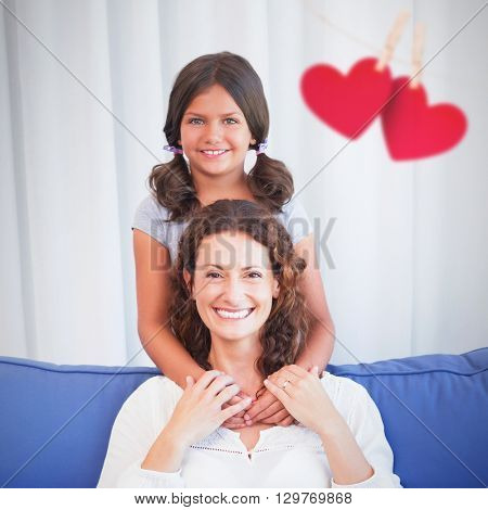 Hearts hanging on a line against happy mother and daughter smiling at camera