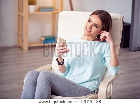 A real music fan. Pleasant content attractive woman sitting in the chair and listening to music while resting