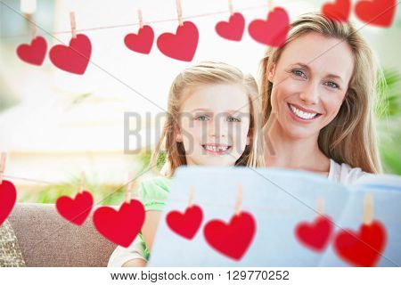 Hearts hanging on a line against happy family posing together