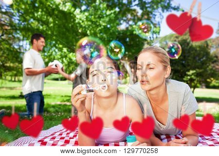 Hearts hanging on a line against happy family doing bubbles