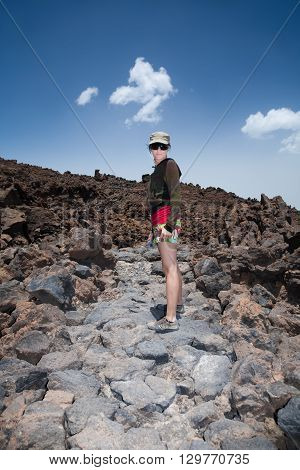 hiker tourist woman with cap green and red clothes posing looking in volcanic ash path to Teide Volcano mountain Tenerife Canary Islands Spain Europe