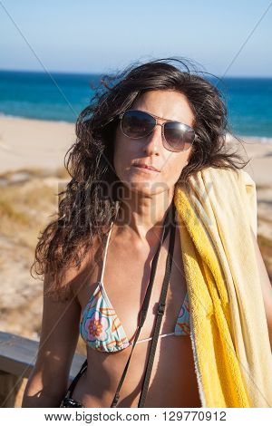 portrait of brunette summer vacation woman with sunglasses bikini and yellow towel posing looking with blue sky in Bolonia sand beach in Tarifa Cadiz Andalusia Spain Europe