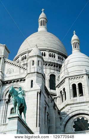 the catholic church Basilica of Sacre Coeur or Sacred Heart with dome and statue of Saint Joan of Arc public monument landmark from year 1914 in Montmartre Paris France Europe