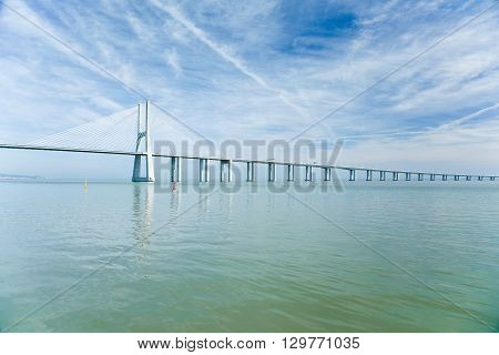 modern bridge named Vasco da Gama the longest in Europe with more than 7 milles over green water Tagus River in Lisbon capital of Portugal