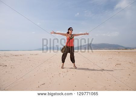 brunette summer vacation woman with sunglasses orange shirt and brown trousers standing open arms up embracing on sand greeting wind in Lances beach Tarifa Cadiz Andalusia Spain Europe