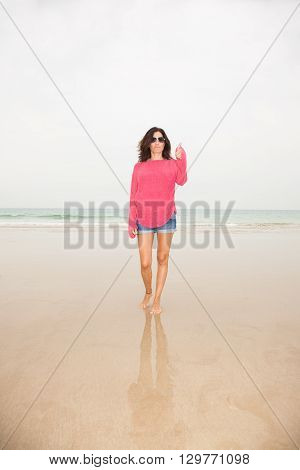 brunette summer vacation woman with sunglasses red sweater blue jeans shorts barefoot standing finger and hand up on sand with ocean behind in beach in Cadiz Andalusia Spain Europe
