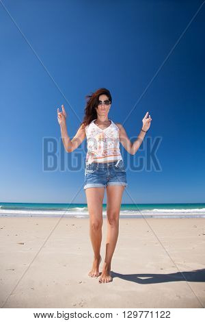 brunette summer vacation woman with sunglasses white shirt and blue jeans shorts standing hand gesturing horns hands on sand with ocean behind in Palmar beach Cadiz Andalusia Spain Europe