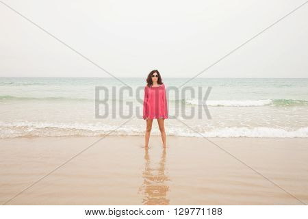 brunette summer vacation woman with sunglasses red sweater blue jeans shorts barefoot standing at seashore on sand with ocean behind in beach in Cadiz Andalusia Spain Europe