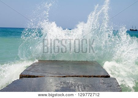 Stone breakwater with breaking waves. Selective focus