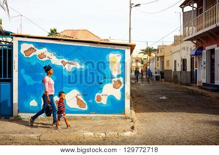 SANTA MARIA, CAPE VERDE - DECEMBER 17, 2015: Cabo Verde map on a wall in Santa Maria Town Sal island. Woman with a child passing by
