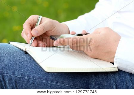 Close up of a man using mobile smart phone and writing by pen