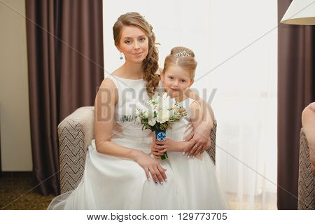 Mother and daughter in the same wedding dresses having fun on the bed