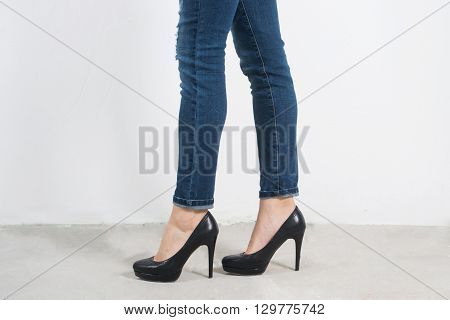 Beautiful female legs with black heels on whote wall.