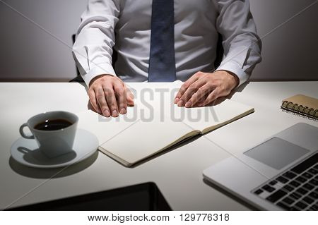 Businessman sitting at office desk with coffee cup keyboard and blank journal