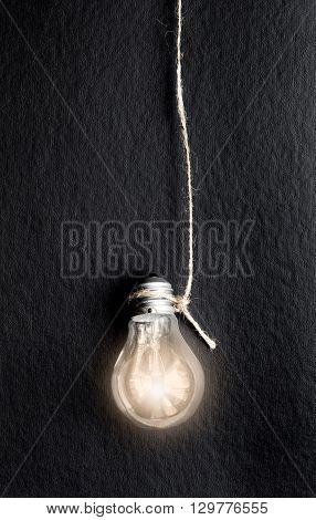 concept of idea illustration lit lamp on black background close up