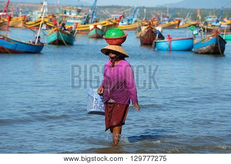 MUI NE, VIETNAM - DECEMBER 25, 2015: Vietnamese woman walks along the coastal strip of the sea with goods on her head. The fishing harbour of Mui ne