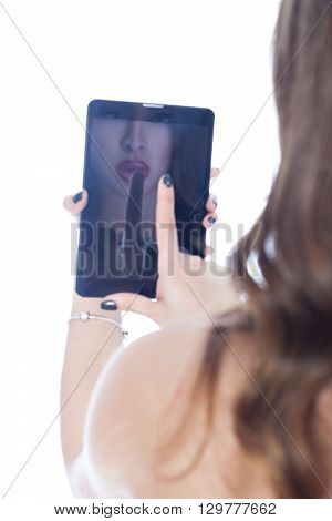 Girl sees herself in the reflection on the computer tablet.