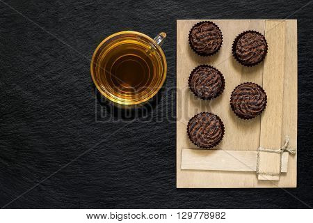 Chocolate mini cakes on a wooden plate and cup of tea on slate surface