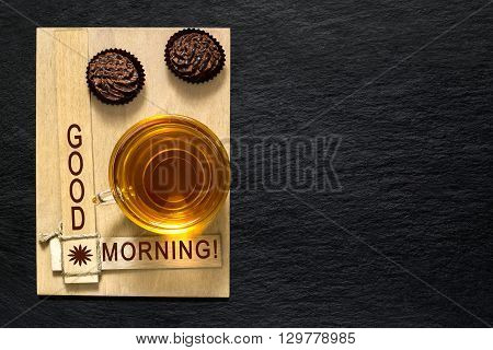 Chocolate mini cakes and a cup of tea on a wooden plate with the inscription: Good morning! Slate background with space for text
