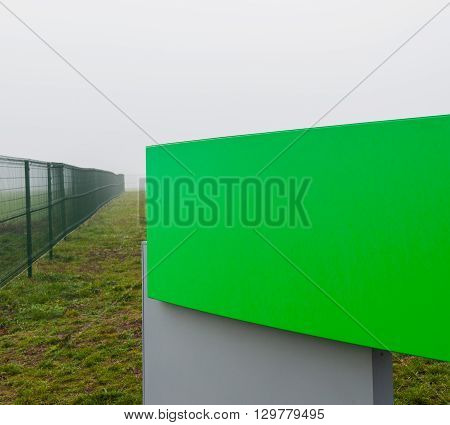 shield and metal fence in a field in the fog rural landscape