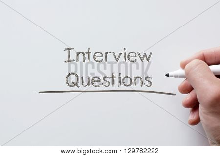 Human hand writing interview questions on whiteboard