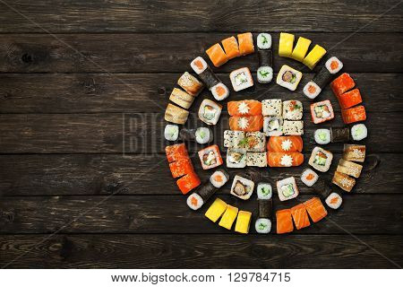 Japanese food restaurant, sushi maki gunkan roll plate or platter set. Set with colorful chopsticks, ginger, soy, wasabi. Sushi at rustic wood background and black stone. Top view with copyspace