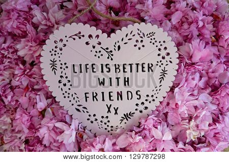 Life is better with friends heart shaped plaque on a pile of blossom