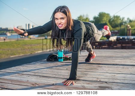 Fit woman doing raised leg plank yoga pilates exercises training her abs core muscles outdoors looking at camera.