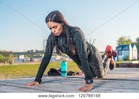 Fitness woman doing knee push-ups or press ups exercise outdoors.