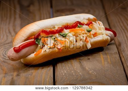 Tasty hot-dog with salad on wooden surface