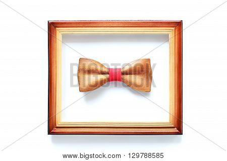 Wooden bowtie in wood frame isolated on white. Hipster, unique, initiative, think different, success story