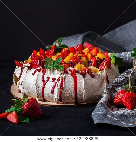 Snow-white meringue Pavlova Cake with fresh strawberries, slices of mango, blueberries and fresh mint on a dark background. Pavlova desert. Whipped cream cheese and mascarpone with berries and fruits