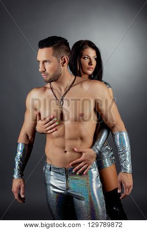 Strip show. Image of bearded man and sexy brunette posing