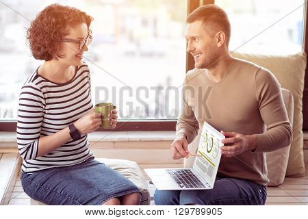 Have a look. Handsome cheerful man holding laptop and showing the screen to his female colleague while working in the office together