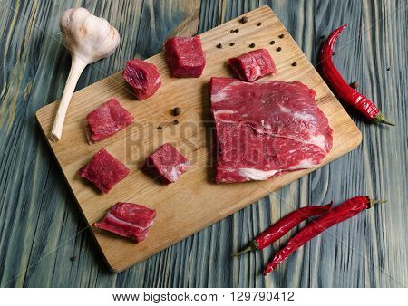 a piece of fresh meat on a cutting board with a knife and pepper