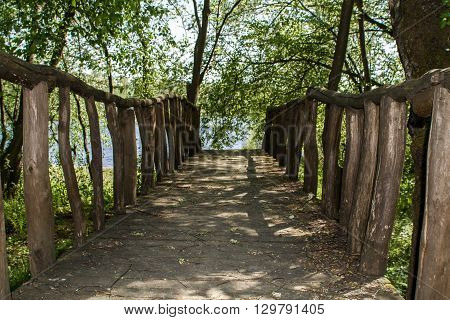 The Leningrad area - 5/15/2016: the wooden bridge in the wood on the bank of the lake