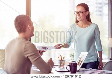 New task for you. Pleasant handsome man sitting at the table and working in the office while getting paper from is smiling beautiful colleague