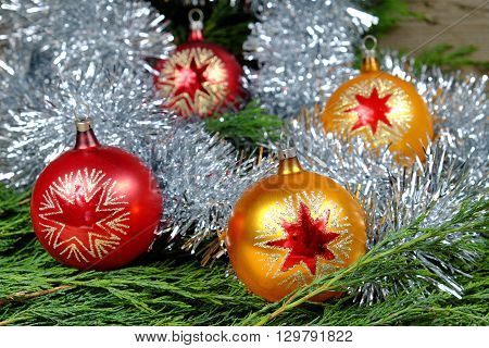 Red and orange Christmas balls with stars around them christmas chain in silver paint on an old wooden table with green needles