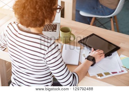 Much tasks to cope with. Pleasant woman sitting at the table and using tablet while working in the office