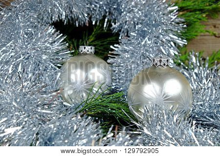 Two silver Christmas balls with silver stars around them christmas chain in silver paint on an old wooden table with green needles