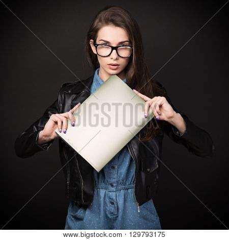 Beautiful young woman. Girl in blue overalls, wearing glasses and a leather jacket. Woman with folders. Sexy girl. High resolution photo. Hd images. Big size.