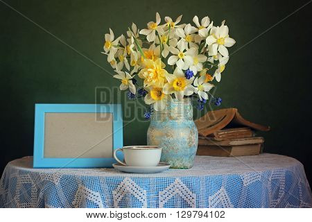 Retro still life with a bouquet of daffodils, a Cup, books, and a photo frame on the table with a tablecloth on a green background. Empty space for Your photo in the frame.