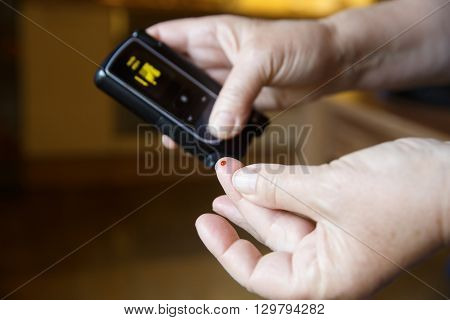 Diabetic patient testing her blood for sugar level at home. Medical process self-diagnose common metabolic widespread and modern epidemic disease concept.