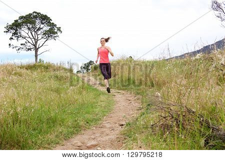 Full Length Portrait Of Athletic Woman Running On Dirt Path