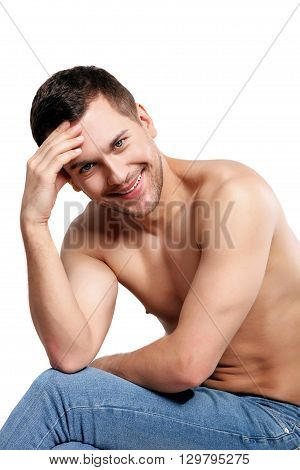 Portrait of cheerful young man sitting with naked torso. He is smiling and looking forward with shame. Isolated