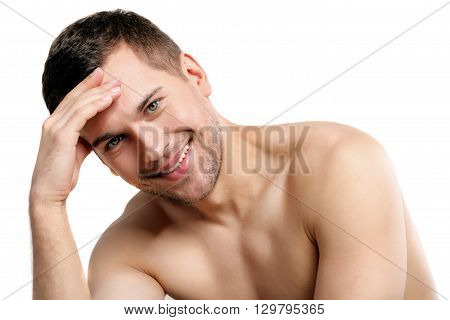 Portrait of cute young guy with bared torso. He is touching arm to forehead and smiling. Man is ashamed. Isolated