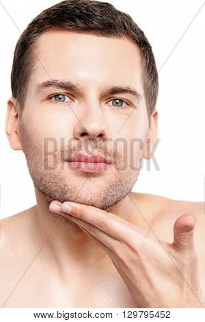 Waist up portrait of handsome man touching his stubble beard. He is standing and looking forward pensively. Isolated