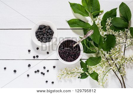Medicinal plant - bird cherry (Prunus padus). Flowering branches dried berries and jam on a white wooden background. Top view