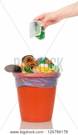 Female hand putting a plastic cup into a bucket of household waste isolated on white background.