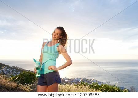 Woman Holding Water Bottle In Front Of Sunset By The Sea
